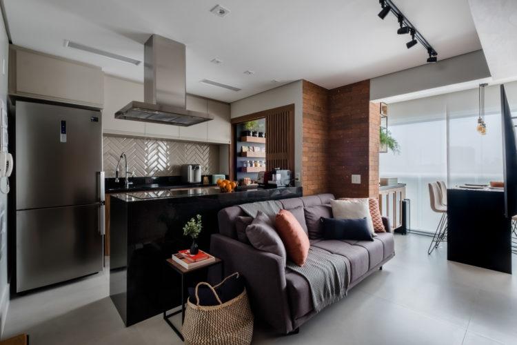 Cozinha aberta e integrada a sala. Bancada do cooktop atrás do sofá e em cima, coifa em inox.