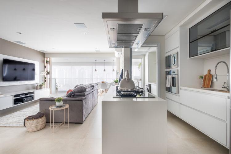 Cozinha aberta e integrada a sala, toda branca. Coifa em inox em cima da ilha
