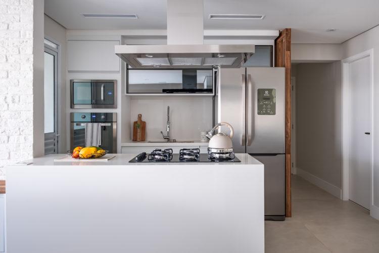 Coifa ou depurador: Profissionais explicam como escolher a melhor opção para o projeto de cozinha. Cozinha integrada a sala, com coifa em inox em cima da ilha.