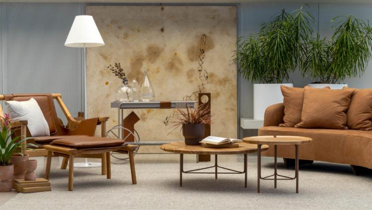 Monique Pampolha e Hannah Cabral assinam a vitrine da loja Lider. Sofá em cor de tijolo, cadeira em couro, mesa de centro em madeira, ao fundo quadro abstrato na cor bege