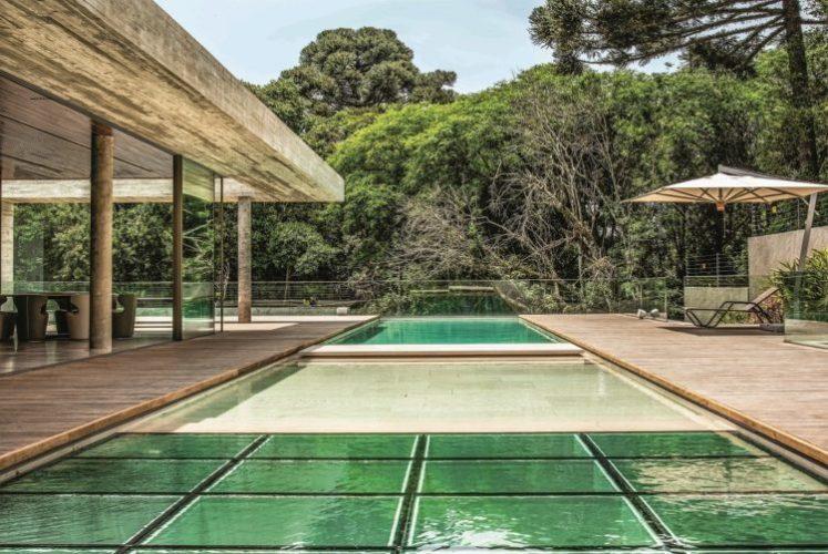 Casa em meio ao verde, com varanda e piscina revestida em pedras naturais