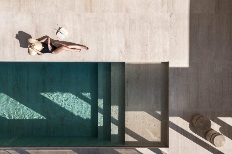 Foto de uma mulher na piscina com o piso revestido em pedra natural