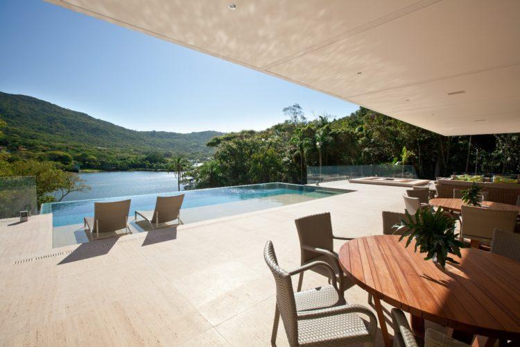 Casa de praia com pedra natural na parte externa, na varanda e na piscina. Vista no mar e montanhas