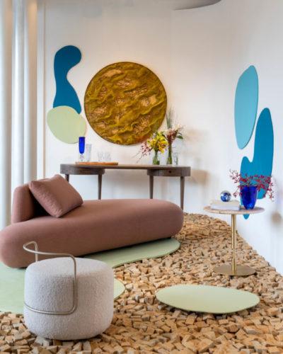 Vitrine de loja decorada com sofá baixo curvo na cor telha e piso com gravetos