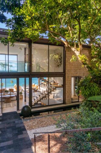 Casa com estrutura metálica e muito vidro, vota para o mar