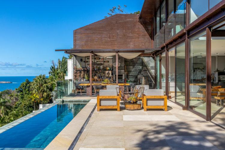 Área da piscina, com uma raia de piscina, e uma cozinha gourmet ao fundo. Vista para o mar e montanhas no Rio de Janeiro