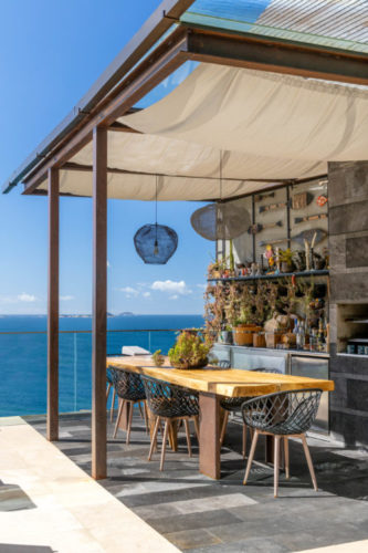 Cozinha gourmet na área da piscina, aberta e com vista para o mar.