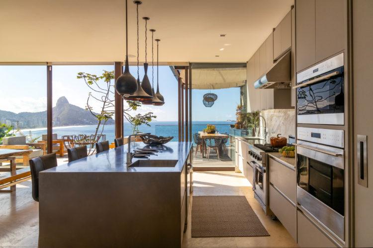 Cozinha integrada a sala, ampla e clara com panos de vidro com vista para o mar
