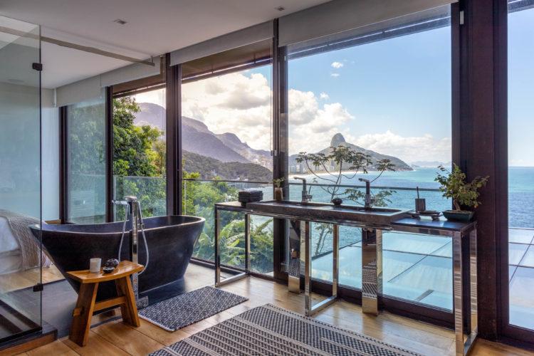 Banheiro com banheira e bancada em frente a janela para o incrível vista para o mar.