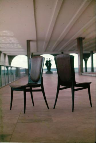 Duas cadeiras em madeira e ao fundo o Palácio do Itamaraty