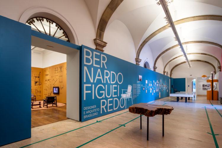 Corredor com um grande painel azul na abertura da exposição sobre Bernardo Figueiredo, designer e arquiteto brasileiro