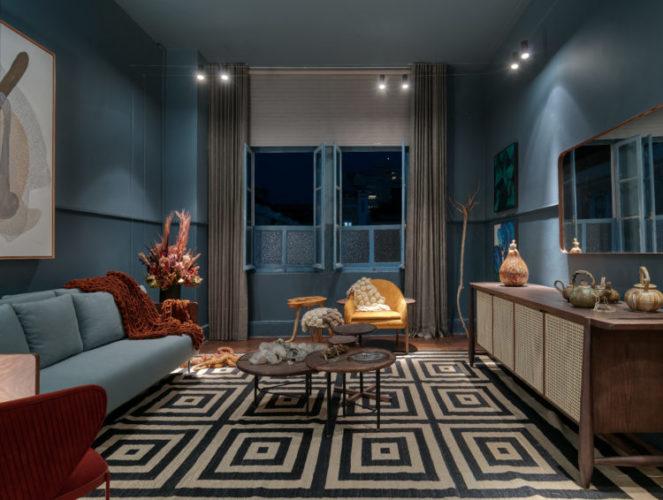 Ambiente da mostra Modernos Eternos em BH. Sala pintada de azul, com sofá azul e tapete preto e branco